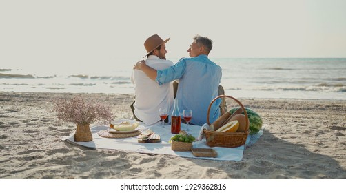 Homosexual lgbt couple, gay men having picnic at the beach, sitting on blanket and embracing, looking to ech other with love