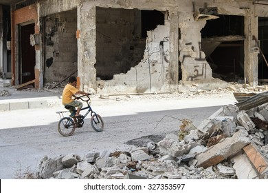 Homs, Syria, September 2013. Boy riding a bicycle among destroyed houses. As a result of fighting between rebels and the SNA, some areas of the city of Homs were damaged.