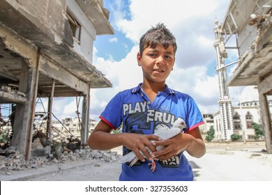Homs, Syria, September 2013. Boy near the destroyed house holding a white dove. As a result of fighting between rebels and the Syrian National Army, some areas of the city of Homs were badly damaged.