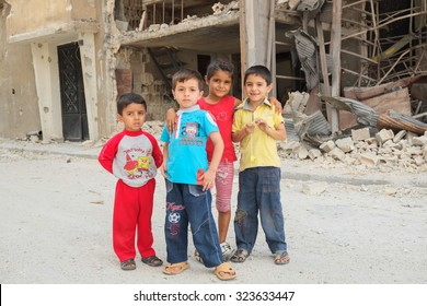 Homs, Syria, September 2013. Children play among the destroyed house in a district of the city of Homs. Several areas of the city of Homs were the scene of fighting between the Syrian army and rebels.