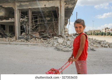 Homs, Syria, September 2013. Girl playing with a baby carriage near the destroyed houses as a result of fighting between rebels and SNA