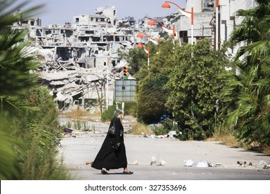 Homs, Syria, September 2013 A woman walks near a residential area in the city of Homs destroyed in the fighting between the rebels of the Syrian National Army