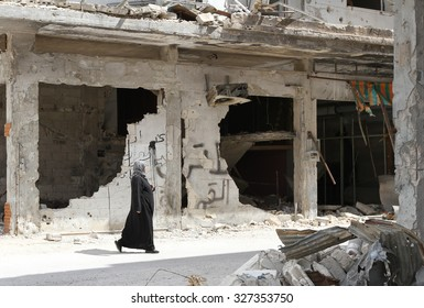Homs, Syria, September 2013 A woman walks near a house in the city of Homs destroyed in the fighting between the rebels of the Syrian National Army