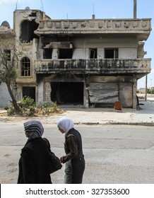 Homs, Syria, September 2013. Women are near the house destroyed in the fighting between the rebels of the Syrian National Army