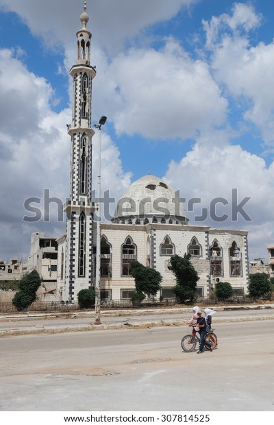 Homs, Syria - September 23: Children pass by a damaged mosque on September 23, 2013 in Homs, Syria. It had been damaged in a fighting between the Syrian National Army and rebels during civil war