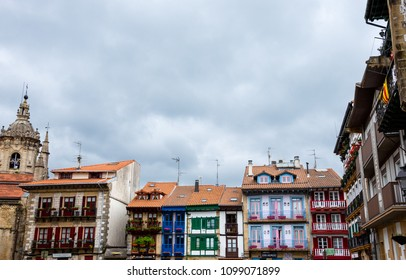 HONDARRIBIA, SPAIN - APRIL 25, 2018: Main square of Hondarribia with its colorful picturesque houses and Parish Church of Santa Maria de La Asuncion y del Manzano at background.