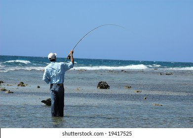 A honduran guide plays a bonefish on the flats on the island of Roatan. Lumps of coral emerge from the flats, and in the background the open sea.