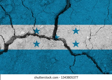 Honduras flag on the cracked earth. National flag of Honduras. Earthquake or drought concept