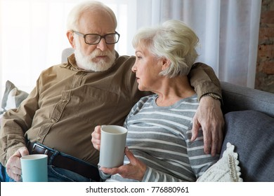 Honest conversation. Portrait of senior couple having dialogue at home while sitting on couch. Husband is cuddling wife while they holding hot cup of tea