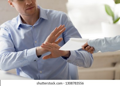 Honest respectable caucasian businessman sitting at desk rejecting money in envelope offered by woman partner cropped close up image. Concept of corruption and bribery law and dark side of business