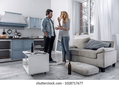 Honest talk. Depressed jobless alcoholic man looking at his emotional worried young wife while standing in the kitchen and having an honest talk with her