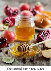 Honey, apple, pomegranate and hala, table set with traditional food for Jewish New Year Holiday, Rosh Hashana