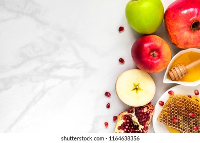 Honey, apple and pomegranate. traditional food for Jewish New Year Holiday, Rosh Hashanah on white marble table. top view with copy space