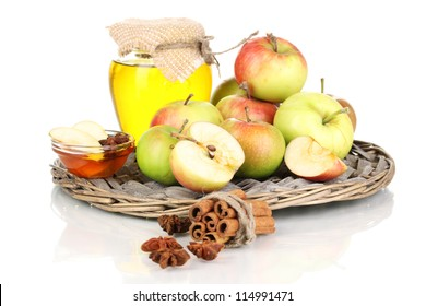 Honey and apples with cinnamon on wicker cradle isolated on white