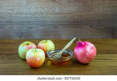 Honey, apples and pomegranates on wood deck for Rosh Hashana celebration.