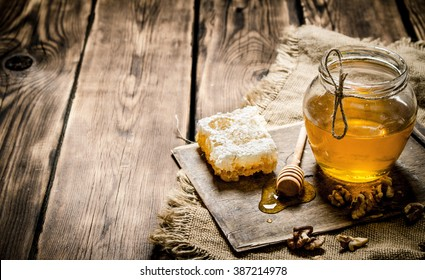 Honey background. Sweet honey in the comb, glass jar with nuts. On wooden background.