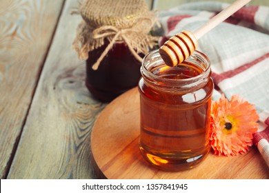 Honey background. Sweet honey in glass jar on wooden background.