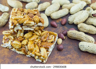 Honey bar with peanuts almonds and hazelnuts surrounded by bunch of roasted and raw peanuts placed on a wooden board