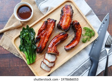 Honey barbecue roast pork on wood tray of wood table - Chinese style grilled pork called Char Siu pork