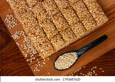 Honey bars with sesame seeds close-up on wooden background. Gozinaki sweets. Traditional oriental confection with roasted caramelized nuts. Sesame seed candy crunch. Energy bars in minimalism style.