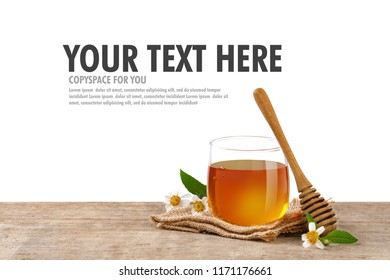 Honey Bee in glass jar with honey dipper and flowers on the wooden table, white background with copy space for your text.