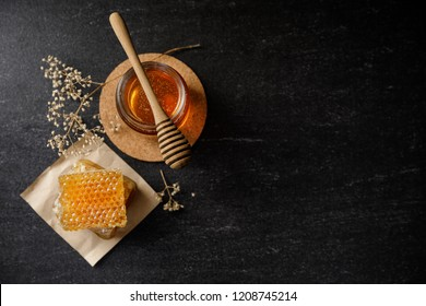 Honey bee and Honeycomb with honey dipper and dry flower on black background, bee products by organic natural ingredients concept