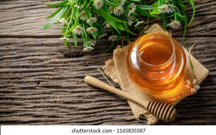 Honey bee in jar with honey dipper and flower on wooden table, bee products by organic natural ingredients concept, copy space for your text