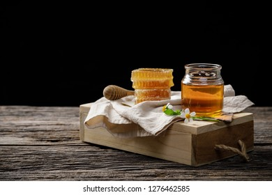 Honey bee in jar and honeycomb with honey dipper and flower on wooden table, bee products by organic natural ingredients concept, copy space for your text