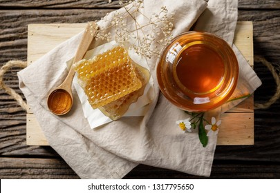 Honey bee in jar and honeycomb with honey dipper and flower on wooden table, bee products by organic natural ingredients concept