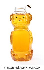 Honey in a bottle shaped like a bear with a bee flying around it