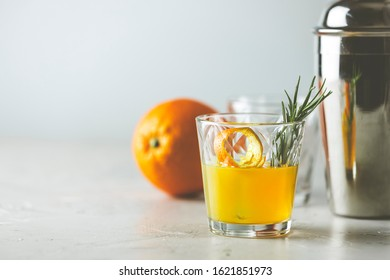 Honey bourbon cocktail with rosemary simple syrup or homemade whiskey sour cocktail drink with orange and rosemary. Decorate orange peel. Light concrete surface.