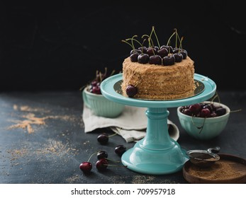 Honey cake with berries on a ceramic dish turquoise color. The background is dark and mysterious. In the background, ceramic tableware, cooking utensils to prepare the dough