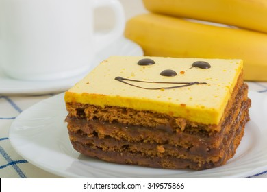 honey cake covered with banana jelly and decorated with chocolate smiley