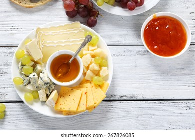 Honey and cheeses on a white plate, food