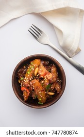 Honey Chilli Potato Wedges, popular Indian-Chinese starter recipe, garnished with sesame and onion. selective focus