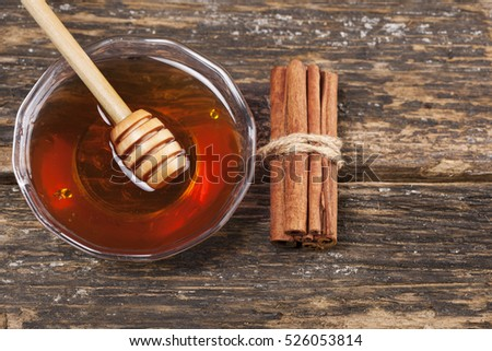 Honey with cinnamon on a wooden background