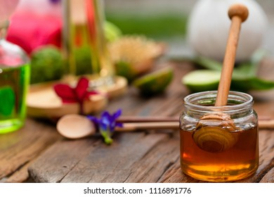 Honey in a clear cup, lay on a wooden floor and have a backdrop of flowers and olive oil and compress the body care concept.