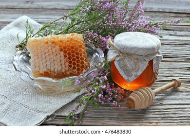 Honey with honey comb and jar of honey with heather on wooden table