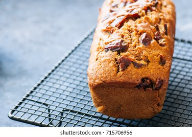 Honey and date spicy cake serving on a wire rack. Blue stone background. Close up and copy space.