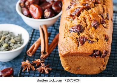 Honey and date spicy cake serving on a wire rack. Blue stone background.