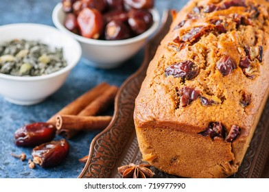 Honey and date spicy cake serving on a vintage tray. Blue stone background.