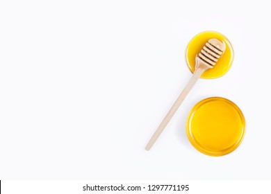 Honey dipper and honey in glass bowl on light grey background. Honey stains. View top
