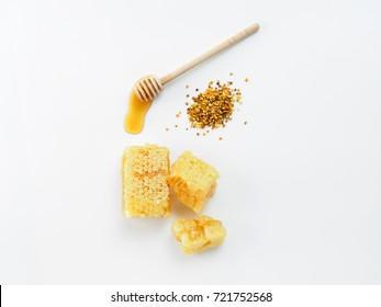Honey with dipper, honeycomb and bee pollen on white background. Top view or flat lay. Copy space.