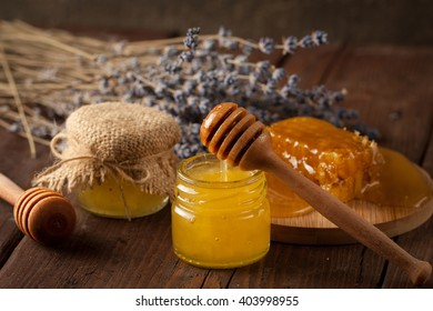 honey dipper and honeycomb with lavender, cinnamon and anise on wooden background. Healthy medical food concept. Natural products.