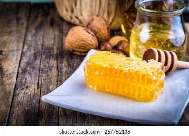 honey dipper and honeycomb, nuts in honey and nuts of various kinds,