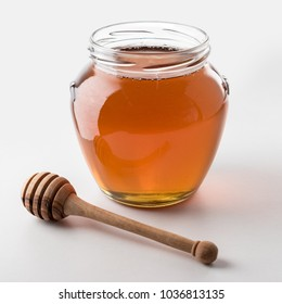 Honey dipper and honey in jar on white background.
