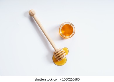 honey dipper and honey jar on white background