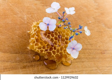 Honey dripping honey comb with flowers on wooden board