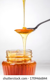 Honey dripping from the honey dipper into a glass jar. Close up. Healthy organic coarse honey dipping from the wooden honey spoon.