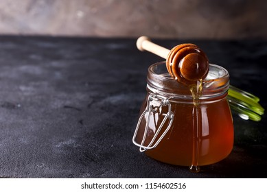 Honey dripping from a dipper into the jar full of fresh honey on dark stone background